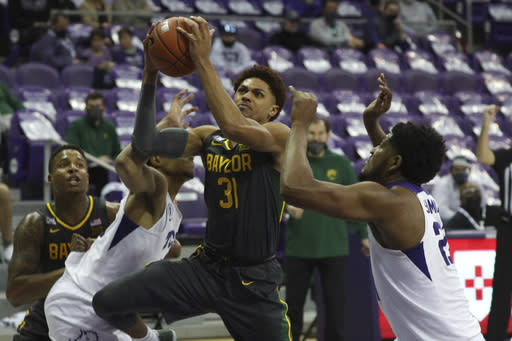 Baylor guard MaCio Teague (31) tries to go up for a shot between TCU forward Chuck O'Bannon Jr. (5) and center Kevin Samuel (21) in the second half of an NCAA college basketball game, Saturday, Jan. 9, 2021, in Fort Worth, Texas. (AP Photo/ Richard W. Rodriguez)