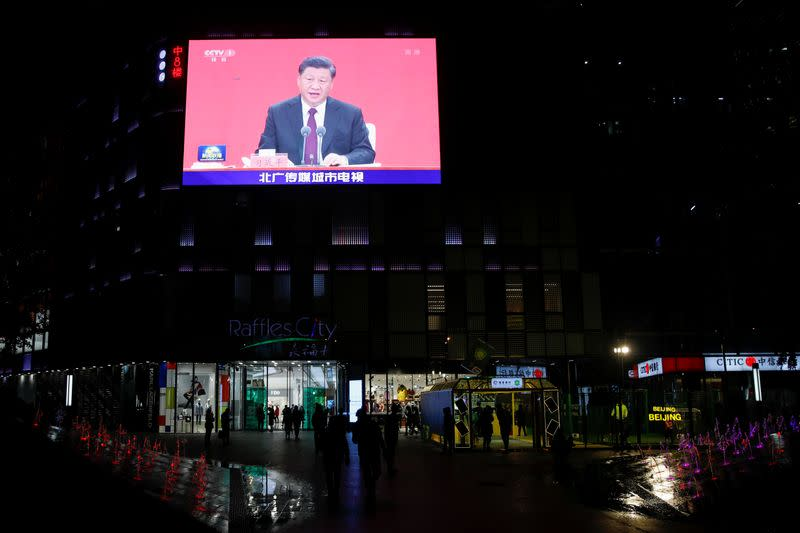 A giant screen shows news footage of Chinese President Xi Jinping speaking at an event marking the 40th anniversary of the establishment of Shenzhen Special Economic Zone, outside a shopping mall in Beijing