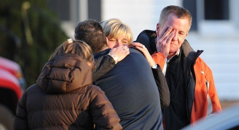 People grieve at the scene of a school shooting in Newtown, Connecticut. A young gunman slaughtered 20 small children and six teachers on Friday after walking into the school in an idyllic town with at least two sophisticated firearms