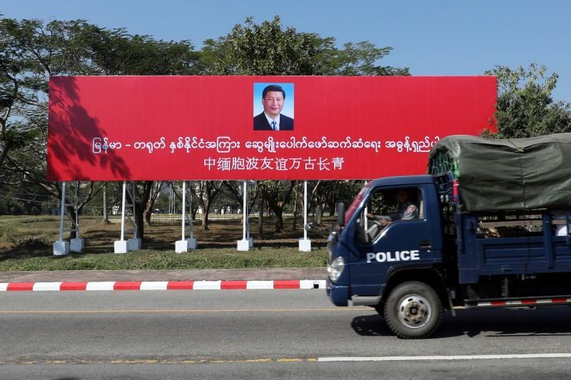 A police van drives by a banner welcoming Chinese President Xi Jinping ahead of his visit to Myanmar in Naypyitaw
