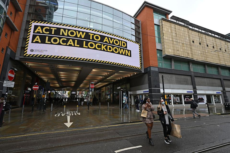 """Shoppers wearing face coverings due to COVID-19 pass beneath an electronic sign reminding pedestrians to """"act now to avoid a local lockdown"""" outside the Arndale Centre in Manchester, northern England on October 6, 2020, after localised restrictions were introduced across northwest following a spike in coronavirus cases. - More than 42,000 people confirmed to have Covid-19 have died in Britain, the worst toll in Europe. (Photo by Paul ELLIS / AFP) (Photo by PAUL ELLIS/AFP via Getty Images)"""