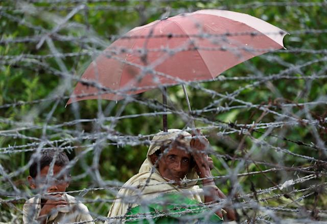 <p>A Rohingya refugee woman and boy looks on through barbed wire as they wait for boat to cross the border through Naf river in Maungdaw, Myanmar, Sept. 7, 2017. (Photo: Mohammad Ponir Hossain/Reuters) </p>