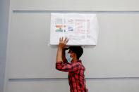 A worker carries a package of Oxford-Astrazeneca COVID-19 vaccines that arrived from India as a gift to Bangladesh, in Dhaka