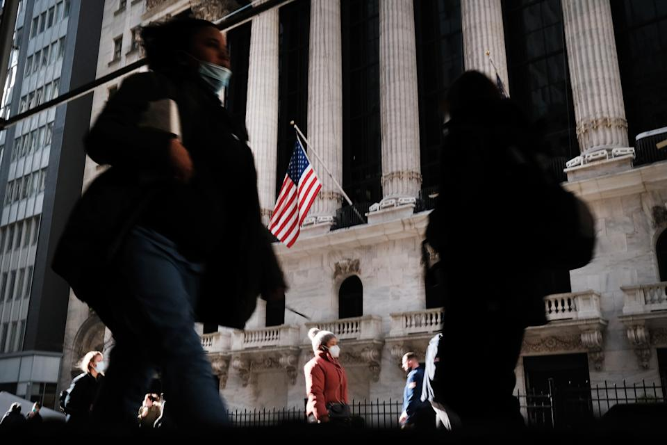 NEW YORK, NEW YORK - NOVEMBER 24: People walk past the New York Stock Exchange (NYSE) on November 24, 2020 in New York City. As investor's fear of an election crisis eases, the DowJones Industrial Average passed the 30,000 milestone for the first time on Tuesday morning.  (Photo by Spencer Platt/Getty Images)