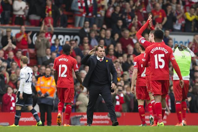 Liverpool's manager Brendan Rodgers, centre, celebrates with his players after their 4-0 win against Tottenham in their English Premier League soccer match at Anfield Stadium, Liverpool, England, Sunday March 30, 2014. (AP Photo/Jon Super)
