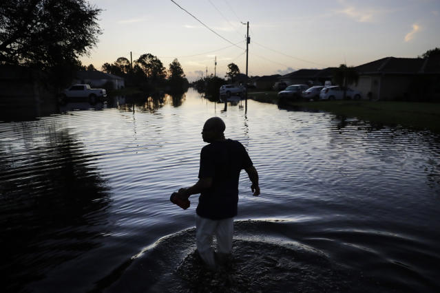 """<p>Jean Chatelier walks through a flooded street from Hurricane Irma to retrieve his uniform from his house to return to work today at a supermarket in Fort Myers, Fla., Sept. 12, 2017. Chatelier walked about a mile each way in knee-high water as a Publix supermarket was planning on reopening to the public today. """"I want to go back to work. I want to help,"""" said Chatelier. (Photo: David Goldman/AP) </p>"""