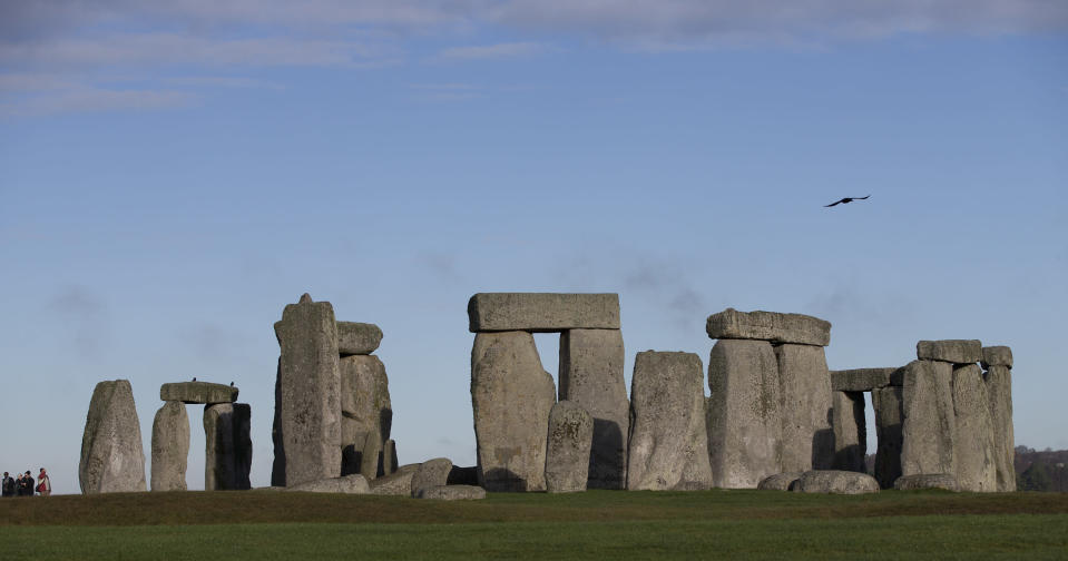 FILE - In this Tuesday, Dec. 17, 2013 file photo, visitors take photographs of the world heritage site of Stonehenge, England. The British government went against the recommendations of planning officials when it gave its consent Thursday Nov. 12, 2020, to controversial plans for a road tunnel to be built near the prehistoric monument of Stonehenge in southern England in order to ease congestion along a stretch widely prone to gridlock. (AP Photo/Alastair Grant, File)