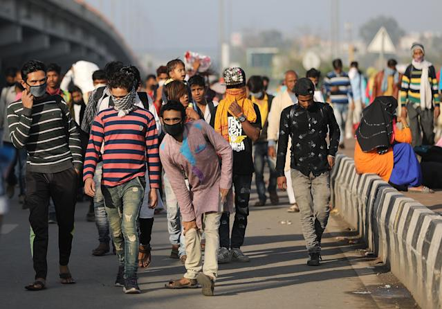 NEW DELHI, INDIA - MARCH 28: Migrant workers along with their family members walk to their villages amid the nationwide lockdown, in wake of coronavirus (COVÄ°D-19) pandemic, at Delhi Uttar Pradesh Border, in New Delhi on March 28, 2020. (Photo by Amarjeet Kumar Singh/Anadolu Agency via Getty Images)