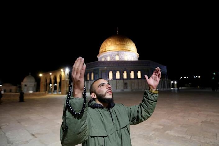 A man prays in front of the Dome of the Rock at the Al-Aqsa mosque compound, which reopened on Sunday (AFP Photo/Ahmad GHARABLI)