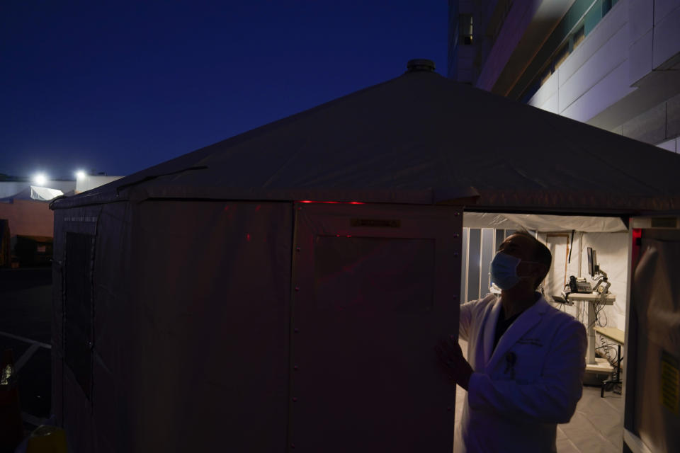 Dr. Jim Keany, an emergency medicine specialist, shuts the door of a triage tent set up to treat COVID-19 patients at Mission Hospital in Mission Viejo, Calif., Monday, Dec. 21, 2020. (AP Photo/Jae C. Hong)