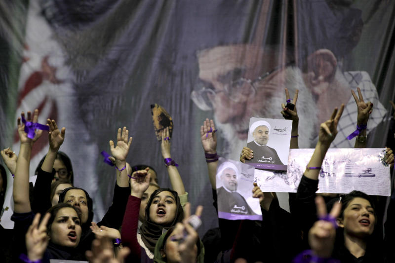 Female supporters of the Iranian presidential candidate, Hasan Rowhani, chant slogans, under a portrait of the Supreme Leader Ayatollah Ali Khamenei, during a campaign rally in Tehran, Iran, Saturday, June 8, 2013. Rowhani, a candidate in next week's presidential elections, says he will reset Iran's economy and will reverse President Mahmoud Ahmadinejad's foreign policy directions if elected. (AP Photo/Ebrahim Noroozi)