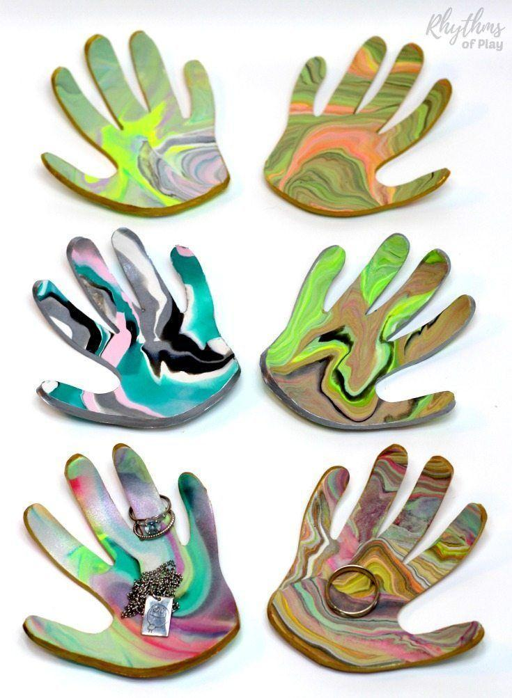 "<p>Need a new way to memorialize your kids' hands? This pretty jewelry tray in the shape of her kids' handprint is sure to make mom shed a tear (in a good way!) </p><p><em><a href=""https://rhythmsofplay.com/marbled-clay-jewelry-dish-keepsake-craft-and-gift/"" rel=""nofollow noopener"" target=""_blank"" data-ylk=""slk:Get the tutorial at Rhythms of Play »"" class=""link rapid-noclick-resp"">Get the tutorial at Rhythms of Play »</a></em> <br></p>"