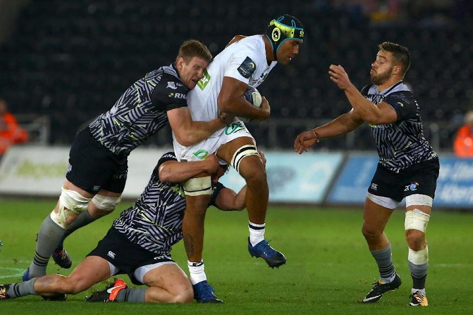 Clermont's Sebastien Vahaamahina (C) is tackled by Ospreys' Justin Tipuric, Dan Lydiate and Rhys Webb (R) during their European Champions Cup round 1 pool match, at Liberty Stadium in Swansea, Wales, on October 15, 2017 (AFP Photo/Geoff CADDICK)