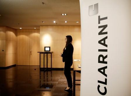 FILE PHOTO: Woman stands next to logo of Swiss specialty chemicals company Clariant ahead of a news conference to present full-year results in Zurich