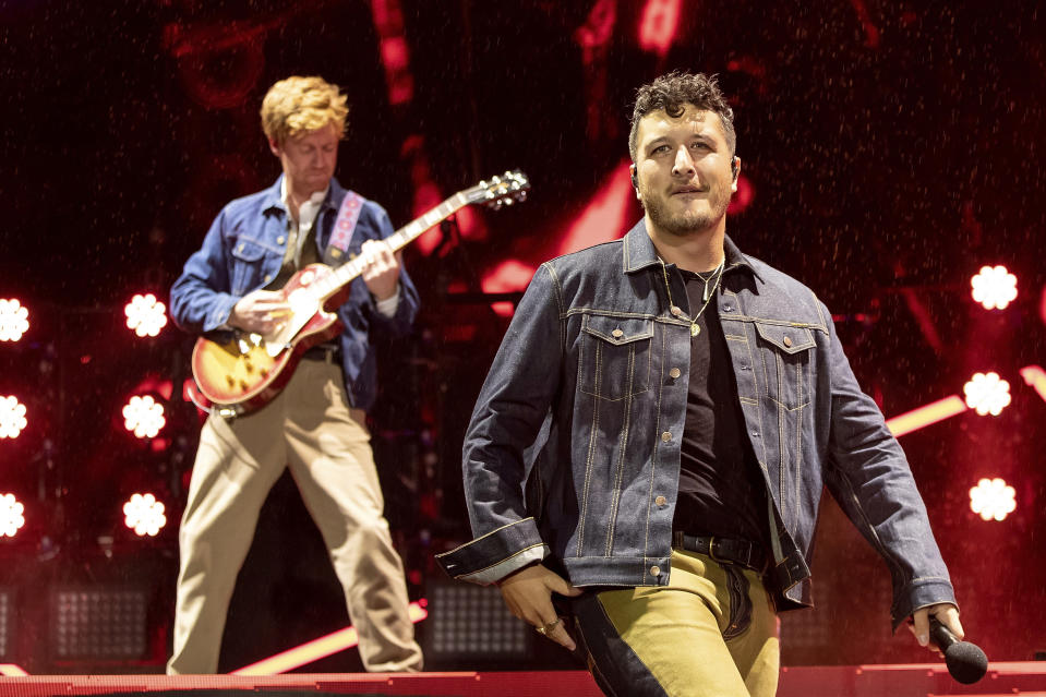 Ji Fraser, left, and Matiu Walters, of New Zealand band Six60, perform at Eden Park in Auckland, New Zealand, Saturday, April 24, 2021. Six60 is being billed as the biggest live act in the world since the coronavirus pandemic struck after New Zealand stamped out the spread of the virus, allowing life to return to normal. On Saturday, the band played a remarkable finale to their latest tour, performing in front of 50,000 people at the first-ever concert at Auckland's Eden Park.(AP Photo/David Rowland)