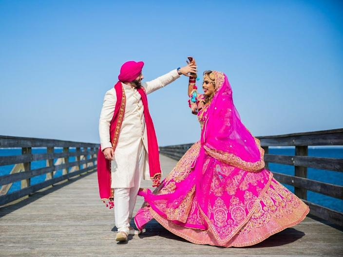A groom and bride dance on a boardwalk wearing traditional Indian wedding attire.
