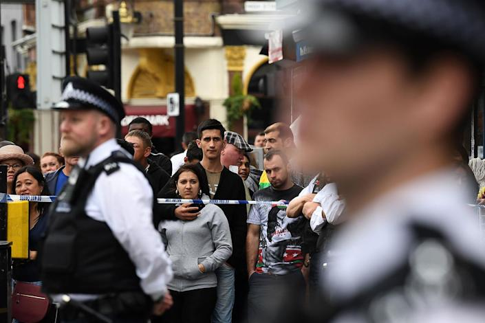 <p>People stand beyond a police cordon outside a row of stores in East Ham in London, June 4, 2017, following a raid as police continue their investigations following the June 3 terror attacks in central London. (Photo: Justin Tallis/AFP/Getty Images) </p>
