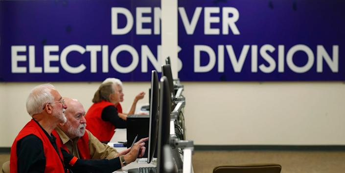Election judges look over ballots during a media tour of the Denver Elections Division headquarters