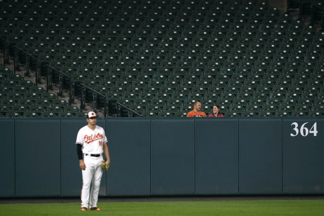 A pair of spectators sit in outfield seats behind Baltimore Orioles left fielder Trey Mancini in the first inning of a baseball game between the Orioles and the Toronto Blue Jays, Monday, Sept. 17, 2018, in Baltimore. (AP Photo/Patrick Semansky)