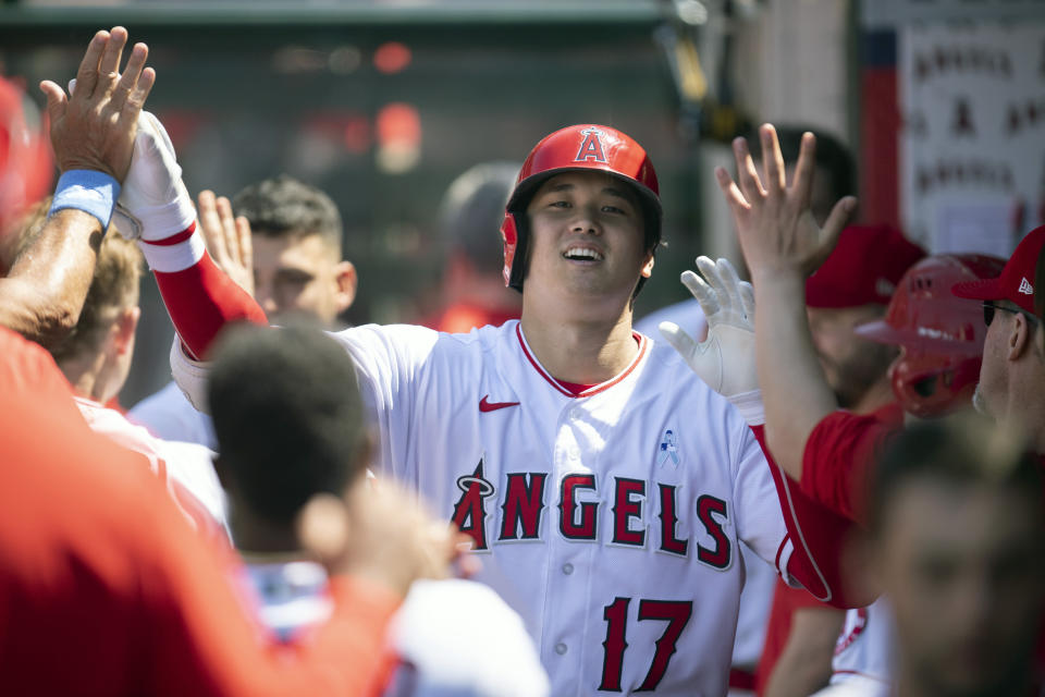 Los Angeles Angels' Shohei Ohtani is greeted in the dugout after hitting a two-run home run during the fifth inning of a baseball game against the Detroit Tigers in Anaheim, Calif., Sunday, June 20, 2021. (AP Photo/Kyusung Gong)