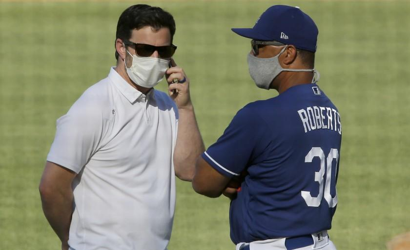 LOS ANGELES, CALIF. - JULY 3, 2020. Dodgers general manager Andrew Friedman, left, and manager Dave Roberts talk during practice at Dodger Stadium on Friday, July 3, 2020. (Luis Sinco/Los Angeles Times)