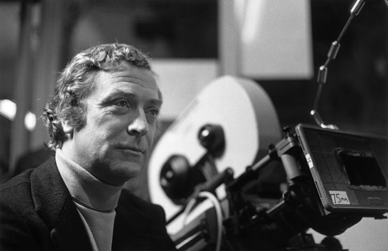 1980: British actor Michael Caine stands next to a 75mm motion picture camera on the set of director Brian De Palma's film, 'Dressed to Kill'. Caine wears a turtleneck sweater and a blazer. (Photo by Hulton Archive/Getty Images)