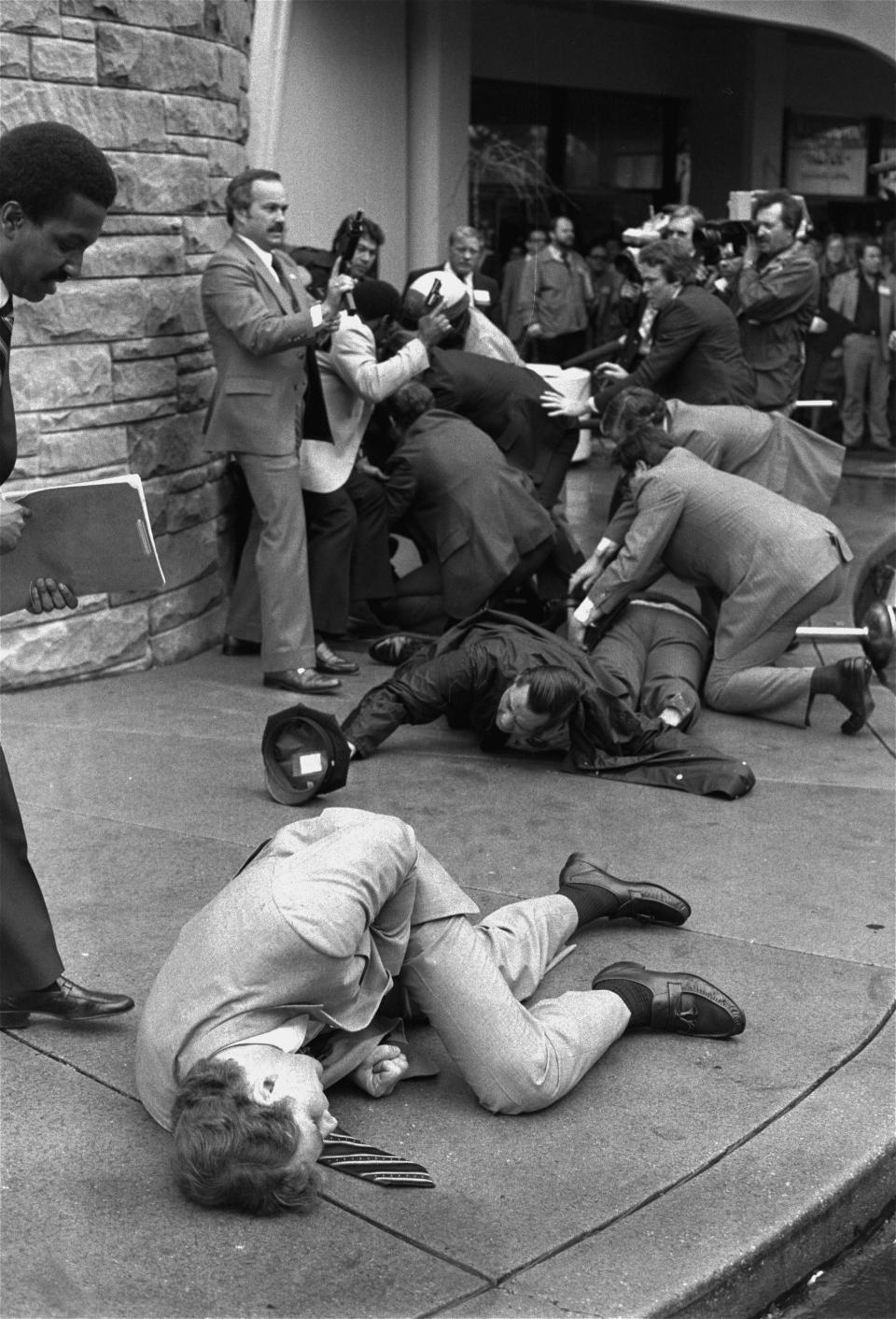 FILE - In this March 30, 1981, file photo, Secret Service agent Timothy J. McCarthy, foreground, Washington policeman Thomas K. Delehanty, center, and presidential press secretary James Brady, background, lie wounded on a street outside a Washington hotel after shots were fired at U.S. President Ronald Reagan. Lawyers for John Hinckley Jr., the man who tried to assassinate Reagan, are scheduled to argue in court Monday, Sept. 27, 2021, that the 66-year-old should be freed from restrictions placed on him after he moved out of a Washington hospital in 2016. (AP Photo/Ron Edmonds, File)