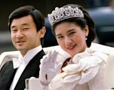 FILE PHOTO: Crown Princess Masako waves to Imperial Household staff alongside Crown Prince Naruhito as they depart for their wedding parade to Togu Palace from the Imperial Palace in Tokyo