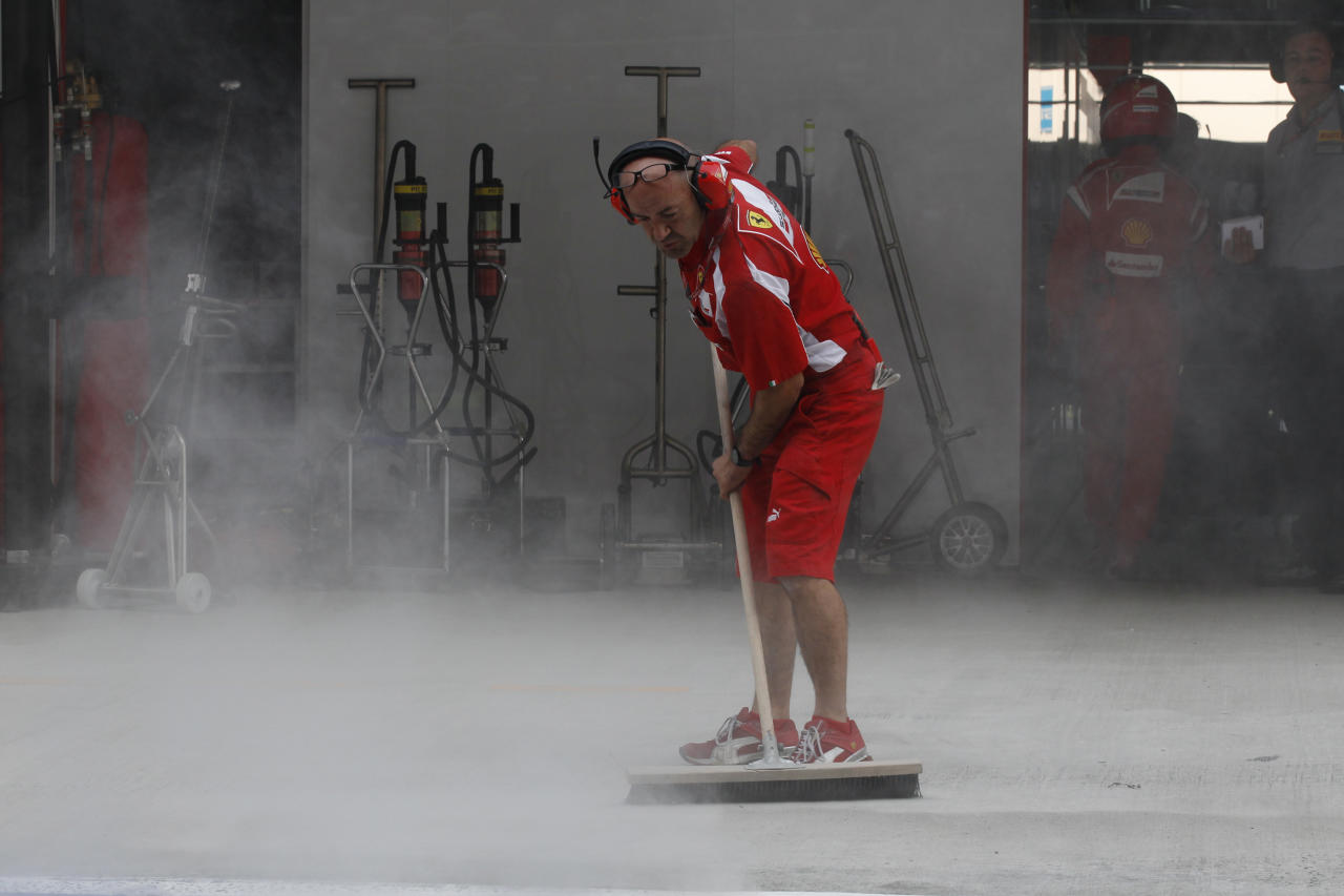 A Ferrari crew sweeps their pit during Indian Formula One Grand Prix at the Buddh International Circuit in Noida, 38 kilometers (24 miles) from New Delhi, India Sunday, Oct. 30, 2011. (AP Photo/Eugene Hoshiko, Pool)