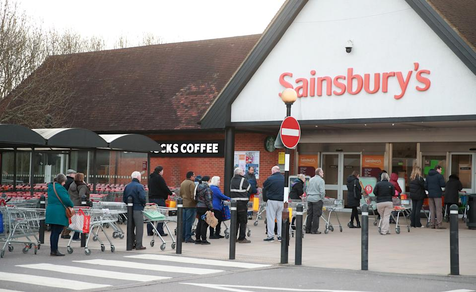 People queuing up outside Sainsburys in Guildford a day after the Chancellor unveiled an emergency package aimed at protecting workers' jobs and wages as they face hardship in the fight against the coronavirus pandemic.