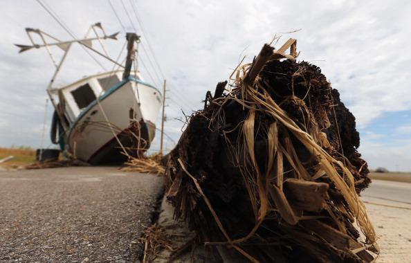 A boat displaced by Hurricane Isaac sits on the edge of a road in lower Plaquemines Parish on September 2, 2012 in Venice, Louisiana. Today was the first day some residents of lower Plaquemines were allowed to return to assess damage to their homes. (Photo by Mario Tama/Getty Images)