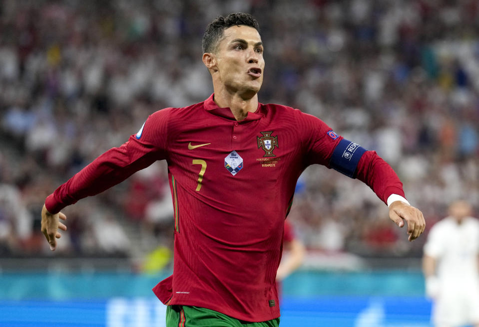 Portugal's Cristiano Ronaldo celebrates after scoring his team's first goal from the penalty spot during the Euro 2020 soccer championship group F match between Portugal and France at the Puskas Arena, Budapest, Hungary, Wednesday, June 23, 2021. (AP Photo/Darko Bandic,Pool)