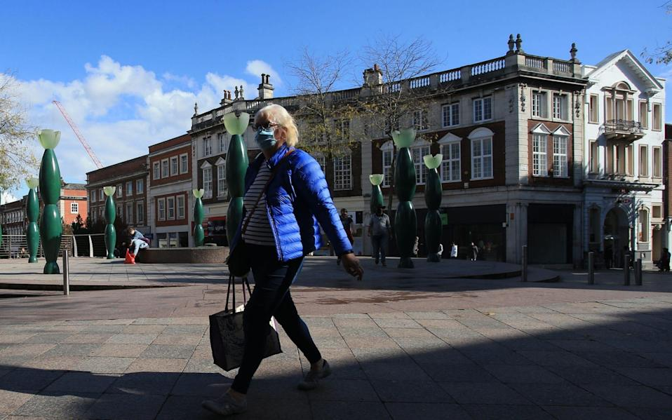 Pedestrians wearing facemasks walk through central Warrington, north west England  - AFP