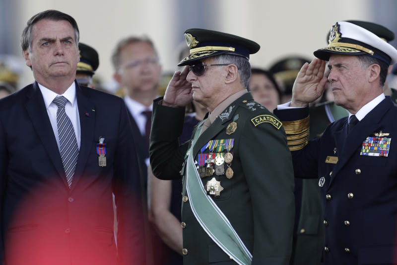 With the red plume of the helmet of an honor guard in the foreground, Brazils President Jair Bolsonaro, left, receives military honors from Army Commander General Edson Leal Pujol, center, during a military ceremony for the Day of the Soldier, at Army Headquarters in Brasilia, Brazil, Friday, Aug. 23, 2019. Brazilian President Jair Bolsonaro says he's leaning toward sending the army to help fight Amazon fires that have alarmed people across the globe. (AP Photo/Eraldo Peres)