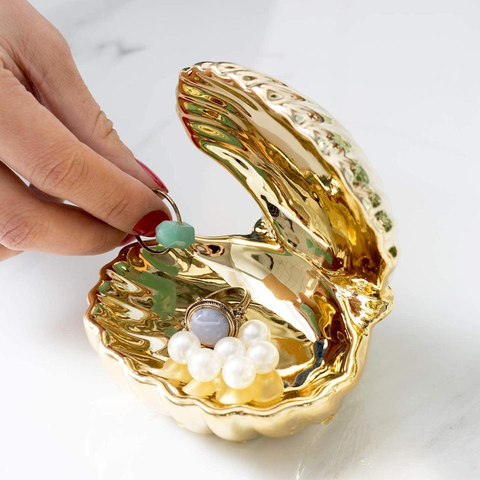 """<h3>Ceramic Shell Jewelry Dish</h3><br>This gilded shell jewelry dish is just tiny enough to pop inside a stocking as a very sweet Christmas-morning surprise.<br><br><strong>WANYA</strong> Ceramic Shell Jewelry Dish, $, available at <a href=""""https://amzn.to/3qlJewu"""" rel=""""nofollow noopener"""" target=""""_blank"""" data-ylk=""""slk:Amazon"""" class=""""link rapid-noclick-resp"""">Amazon</a>"""