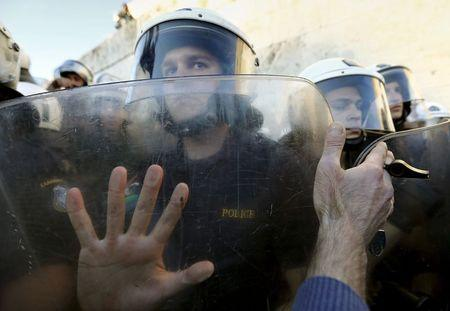 A protester holds a whistle as he places his hand against the shields of riot policemen guarding the parliament building during a rally calling on the government to clinch a deal with its international creditors and secure Greece's future in the Eurozone, in Athens, Greece, June 22, 2015. REUTERS/Yannis Behrakis