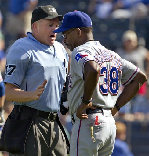 Home plate umpire Mike Everitt (57) talks with Texas Rangers manager Ron Washington (38) during the eighth inning of a baseball game against the Kansas City Royals at Kauffman Stadium in Kansas City, Mo., Monday, Sept. 3, 2012. (AP Photo/Orlin Wagner)