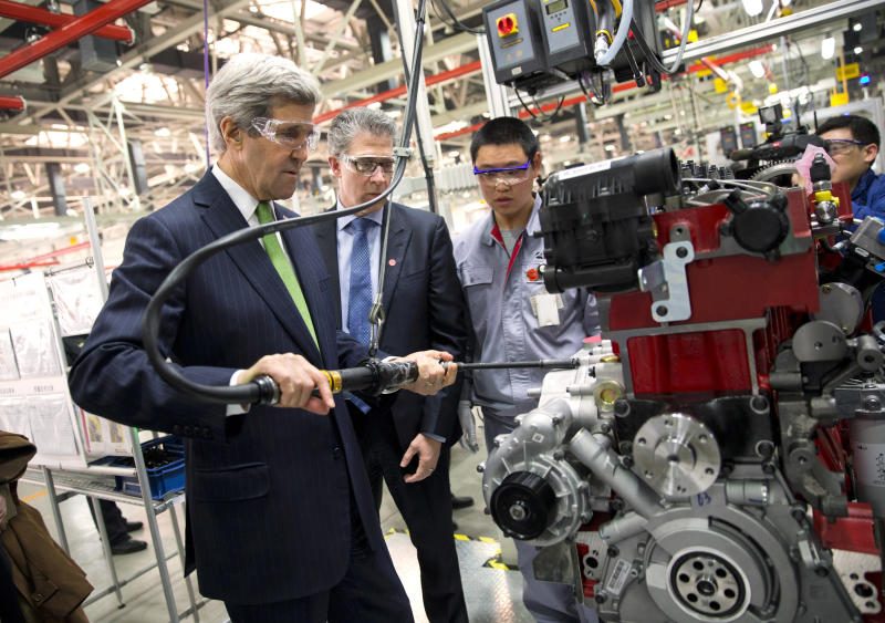 U.S. Secretary of State John Kerry, left, torques an engine bolt during a tour of the Foton Cummins Engine plant in Beijing, China Saturday, Feb. 15, 2014. Kerry toured the plant and made remarks on climate change cooperation between the United States and China. (AP Photo/Evan Vucci, Pool)