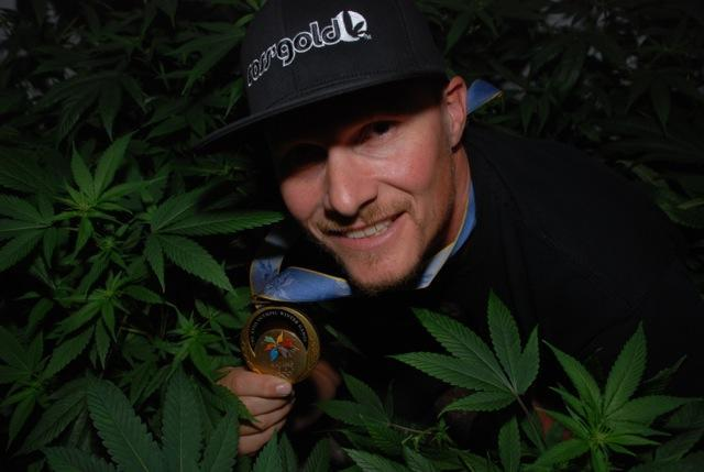 Ross Rebagliati posing with a few cannabis plants, as well as his Olympic gold medal. (Photo: Ross' Gold)