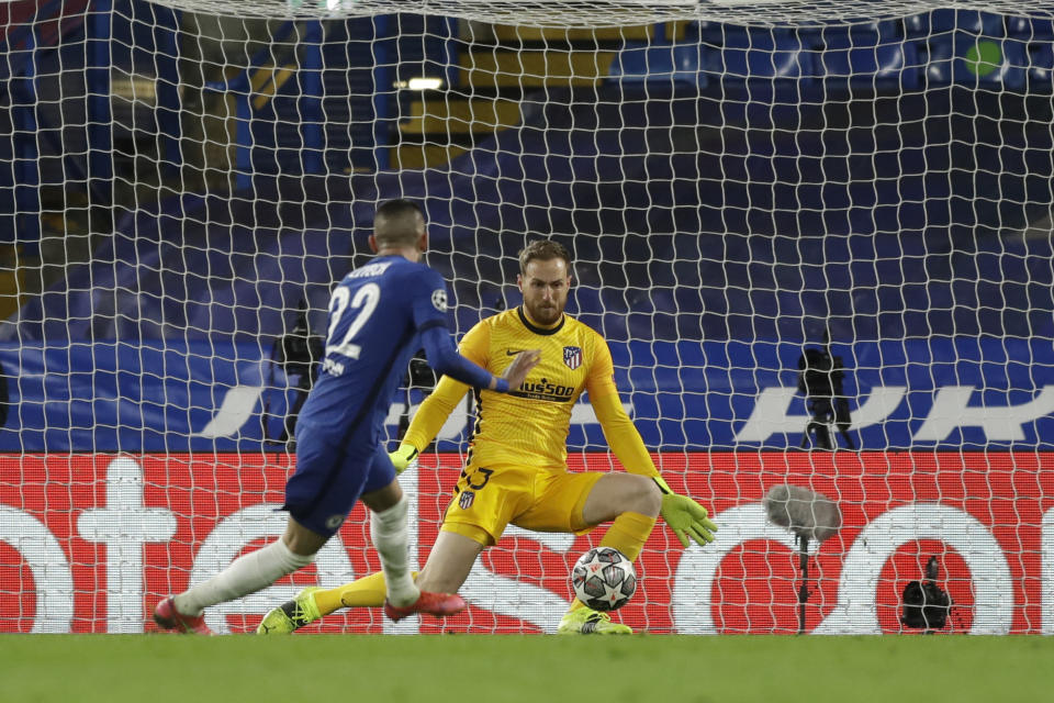 Atletico Madrid's goalkeeper Jan Oblak, right, fails to save the ball as Chelsea's Hakim Ziyech scores his side's opening goal during the Champions League, round of 16, second leg soccer match between Chelsea and Atletico Madrid at the Stamford Bridge stadium, London, Wednesday, March 17, 2021. (AP Photo/Matt Dunham)