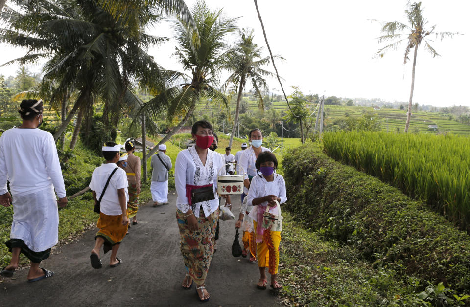 People wearing face masks as a precaution against coronavirus outbreak walk to a temple at a village in Bali, Indonesia Monday, Sept. 21, 2020. (AP Photo/Firdia Lisnawati)
