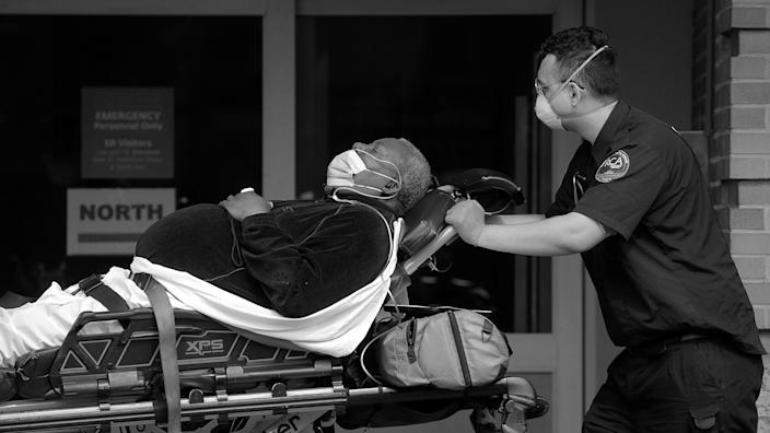 A paramedic takes a patient into an emergency center