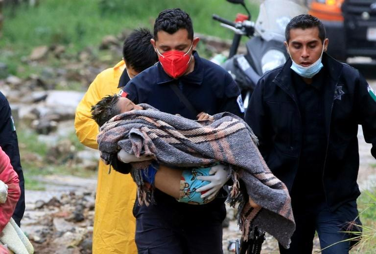A paramedic carries a child after a landslide crushed a house in Xalapa in eastern Mexico during Hurricane Grace