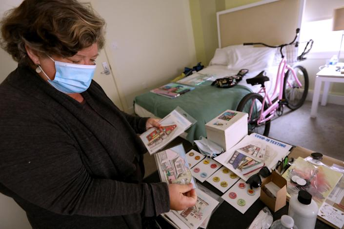 """Artist Wendy Brown looks over her urban sketches in her hotel room. <span class=""""copyright"""">(Genaro Molina / Los Angeles Times)</span>"""