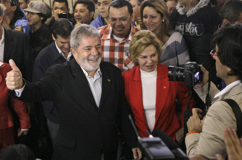 Brazil's President Luiz Inacio Lula da Silva, left, accompanied by his wife Marisa Leticia, center, poses for pictures after voting at a polling station during Brazil's general elections in Sao Bernardo do Campo, Sao Paulo state, Brazil, Sunday, Oct. 3, 2010. Brazilians vote Sunday in national elections that could see front-running candidate Dilma Rousseff become the country's first female president, succeeding Lula, her popular ally and mentor. (AP Photo/Silvia Izquierdo)