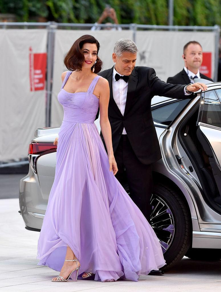 """<p><strong>When: September 2, 2017</strong><br>Amal and George Clooney <a href=""""https://ca.style.yahoo.com/amal-clooney-goes-old-hollywood-versace-143728971.html"""" data-ylk=""""slk:made an appearance;outcm:mb_qualified_link;_E:mb_qualified_link;ct:story;"""" class=""""link rapid-noclick-resp yahoo-link"""">made an appearance</a> at the 74th annual Venice Film Festival on Saturday for the premiere of Clooney's crime-comedy flick """"Suburbicon."""" While George opted for a classic Armani tux, Amal stunned in a floor-sweeping silk chiffon lilac Versace gown. <em>(Photo: Getty)</em> </p>"""