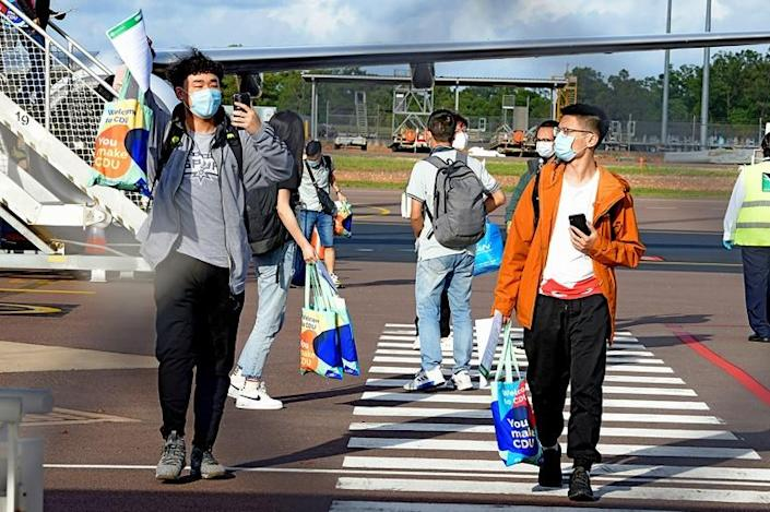Foreign students disembark from an international flight at Darwin Airport, the first such arrivals since Australia's border closure in March
