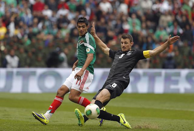 Mexico's Raul Jimenez, left, fights for the ball with New Zealand's Tommy Smith during a 2014 World Cup playoff first round soccer match in Mexico City, Wednesday, Nov. 13, 2013. (AP Photo/Eduardo Verdugo)