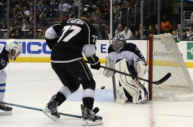 Winnipeg Jets goalie Al Montoya stops a shot on goal as Los Angeles Kings center Jeff Carter watches during the second period of an NHL hockey game Saturday, March 29, 2014, in Los Angeles. (AP Photo/Kevork Djansezian)