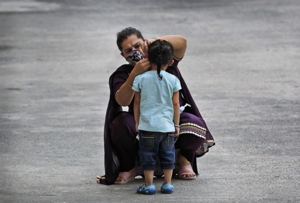 A woman fixes her daughter's face mask at a COVID-19 testing center in New Delhi, India, Saturday, Oct. 3, 2020. India has crossed 100,000 confirmed COVID-19 deaths on Saturday, putting the country's toll at nearly 10% of the global fatalities and behind only the United States and Brazil. (AP Photo/Manish Swarup)
